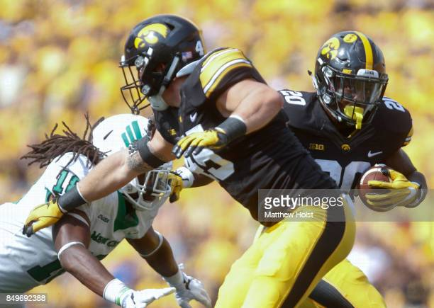 Running back James Butler of the Iowa Hawkeyes rushes up field during the first quarter in front of linebacker Joshua Wheeler of the North Texas Mean...