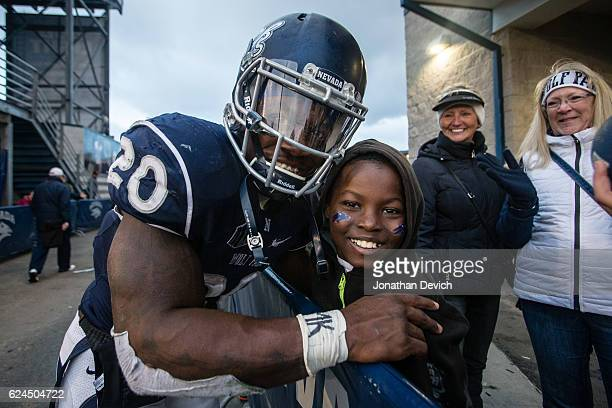 Running back James Butler of the Nevada Wolf Pack poses with a young fan after winning over the Utah State Aggies at Mackay Stadium on November 19...