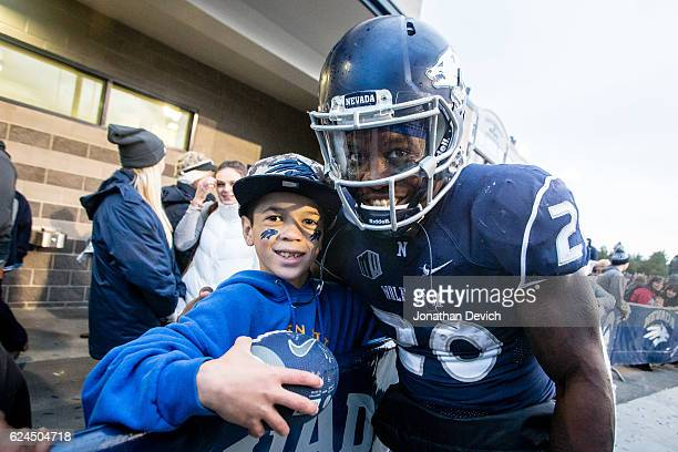 Running back James Butler of the Nevada Wolf Pack stops with a young fan after signing autographs after the win over the Utah State Aggies at Mackay...
