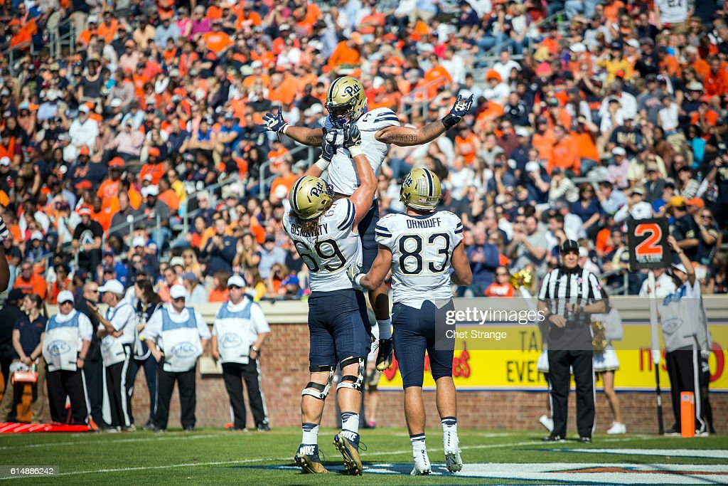 Running back James Conner #24 of the Pittsburgh Panthers is lifted by teammate offensive lineman Adam Bisnowaty #69 during the Panthers' game against the Virginia Cavaliers at Scott Stadium on October 15, 2016 in Charlottesville, Virginia.