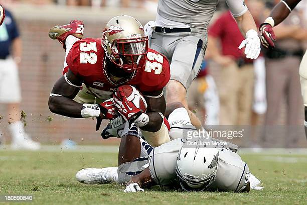 Running back James Wilder Jr #32 of the Florida State Seminoles dives over Cornerback Bryson Keeton of the Nevada Wolf Pack during the game at Doak...