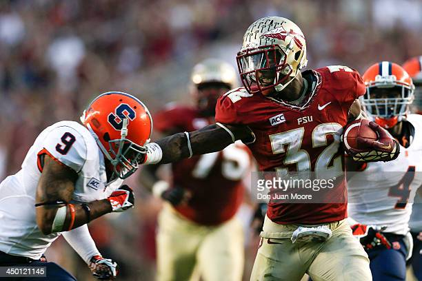 Running back James Wilder Jr #32 of the Florida State Seminoles gives a stiff arm to cornerback Ri'Shard Anderson of the Syracuse Orange during the...
