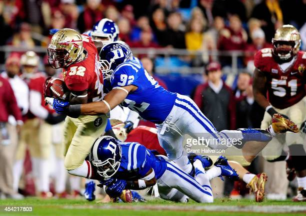 Running back James Wilder Jr #32 of the Florida State Seminoles carries the ball as defensive end Justin Foxx and cornerback Deondre Singleton of the...