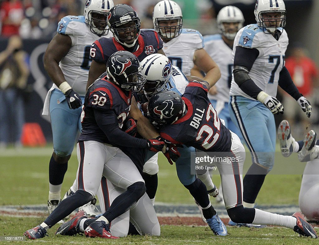 Running back <a gi-track='captionPersonalityLinkClicked' href=/galleries/search?phrase=Javon+Ringer&family=editorial&specificpeople=2168462 ng-click='$event.stopPropagation()'>Javon Ringer</a> #21 of the Tennessee Titans is wrapped up by <a gi-track='captionPersonalityLinkClicked' href=/galleries/search?phrase=Danieal+Manning+-+American+Football+Player&family=editorial&specificpeople=589817 ng-click='$event.stopPropagation()'>Danieal Manning</a> #38 of the Houston Texans and Alan Ball #22 of the Texans at Reliant Arena at Reliant Park on September 30, 2012 in Houston, Texas.