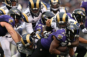 Running back Javorius Allen of the Baltimore Ravens is tackled by defensive tackle Nick Fairley of the St Louis Rams in the fourth quarter at MT Bank...