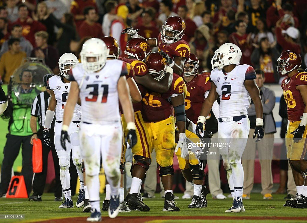 Running back Javorius Allen #37 of the USC Trojans celebrates with teammates after scoring on a four yard touchdown run in the fourth quarter against the Arizona Wildcats at Los Angeles Coliseum on October 10, 2013 in Los Angeles, California. USC won 38-31.