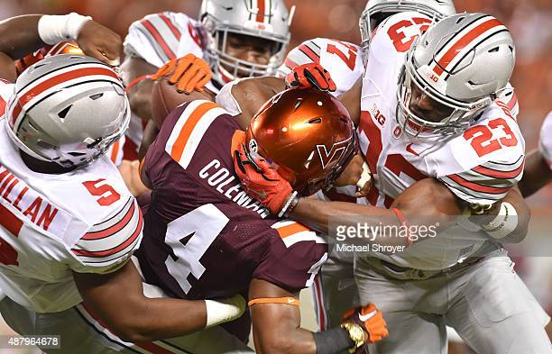Running back JC Coleman of the Virginia Tech Hokies is tackled by safety Tyvis Powell and linebacker Raekwon McMillan of the Ohio State Buckeyes in...