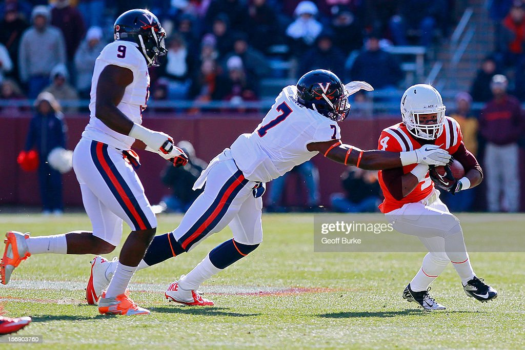Running back J.C. Coleman #4 of the Virginia Tech Hokies runs with the ball as defensive end Eli Harold #7 of the Virginia Cavaliers attempts to make the tackle at Lane Stadium on November 24, 2012 in Blacksburg, Virginia.