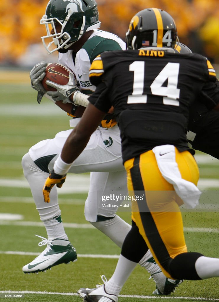 Running back Jeremy Langford #33 of the Michigan State Spartans is brought down during the first quarter by defensive back Desmond King #14 and linebacker Anthony Hitchens #31 of the Iowa Hawkeyes on October 5, 2013 at Kinnick Stadium in Iowa City, Iowa. Michigan State won 26-14.