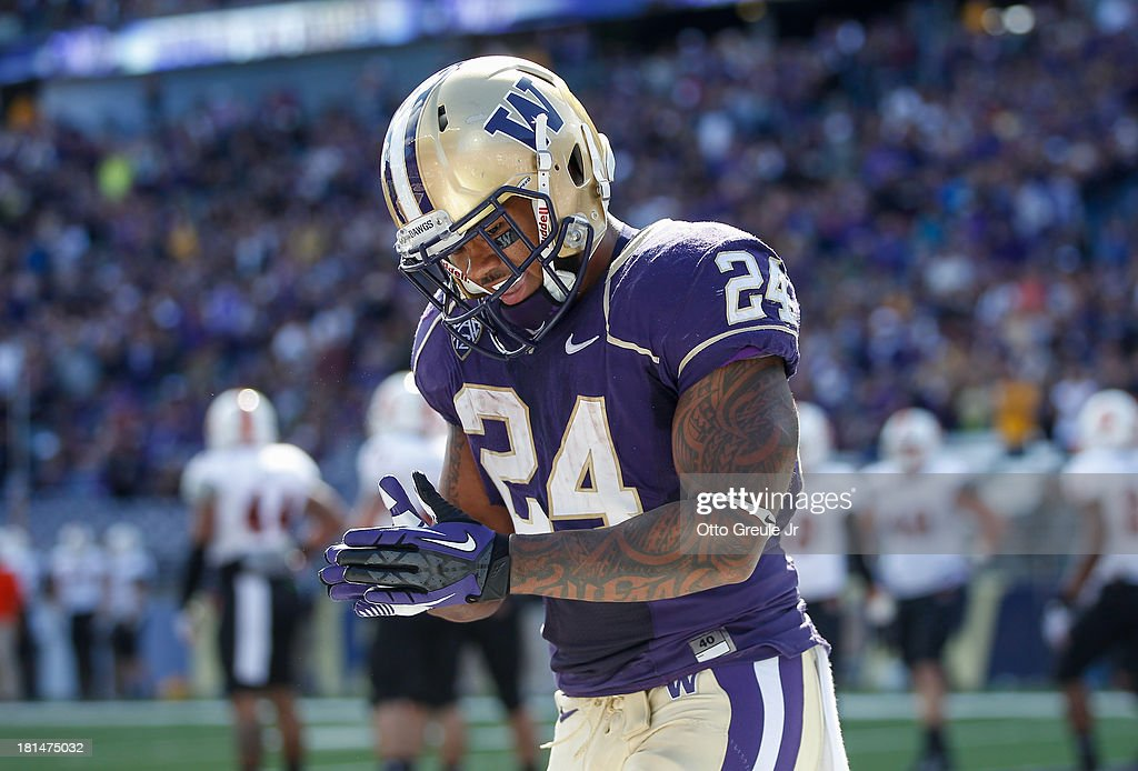 Running back Jesse Callier #24 of the Washington Huskies celebrates after scoring a touchdown against the Idaho State Bengals in the first half on September 21, 2013 at Husky Stadium in Seattle, Washington. The Huskies defeated the Bengals 56-0.