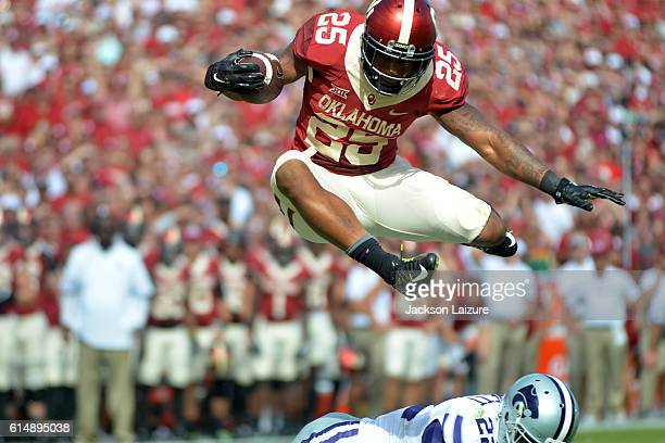 Running back Joe Mixon of the Oklahoma Sooners leaps over safety Dante Barnett of the Kansas State Wildcats on Saturday October 15 2016 at Gaylord...
