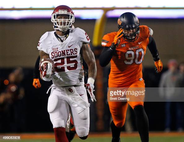 Running back Joe Mixon of the Oklahoma Sooners outruns defensive end Trace Clark of the Oklahoma State Cowboys for a touchdown November 28 2015 at...
