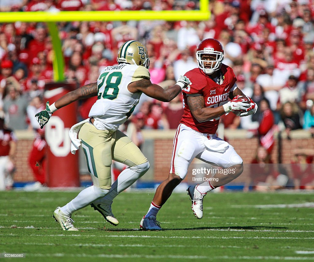 Running back Joe Mixon #25 of the Oklahoma Sooners tries to evade safety Orion Stewart #28 of the Baylor Bears November 12, 2016 at Gaylord Family-Oklahoma Memorial Stadium in Norman, Oklahoma. Oklahoma defeated Baylor 45-24.