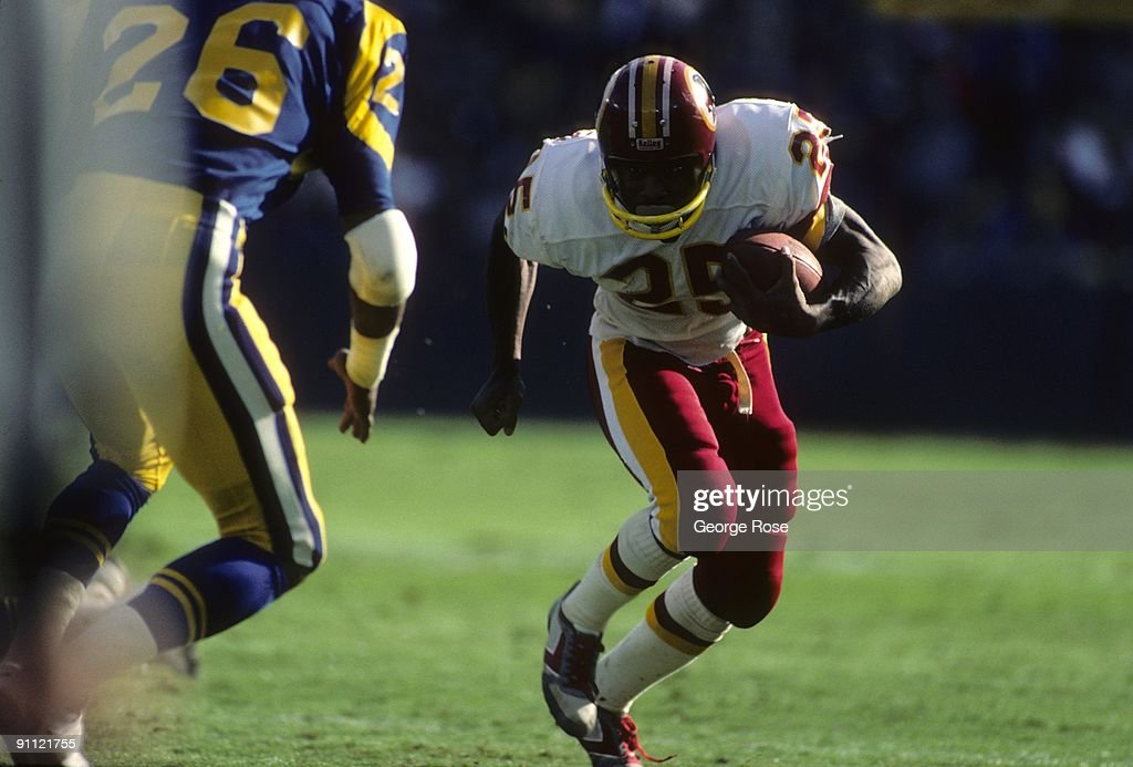 Running back Joe Washington of the Washington Redskins runs with the ball against Eric Harris of the Los Angeles Rams during the game at RFK Stadium...