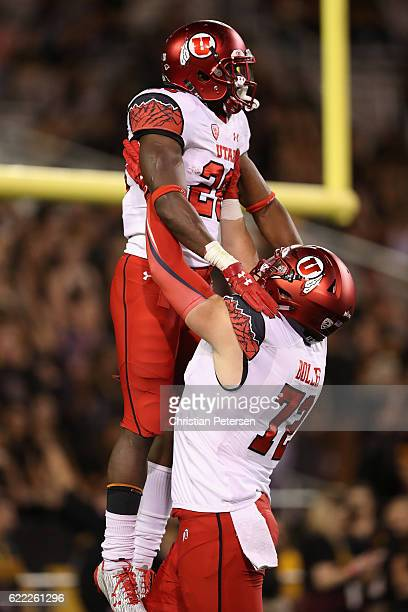 Running back Joe Williams of the Utah Utes celebrates with offensive lineman Garett Bolles after scoring on a 82 yard rushing touchdown against the...