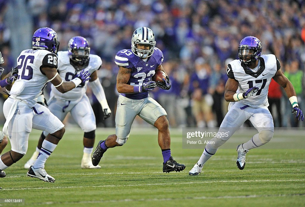 Running back John Hubert #33 of the Kansas State Wildcats rushes up field between defenders Sam Carter #17 and Derrick Kindred #26 of the TCU Horned Frogs during the second half on November 16, 2013 at Bill Snyder Family Stadium in Manhattan, Kansas. Kansas State defeated TCU 33-31.