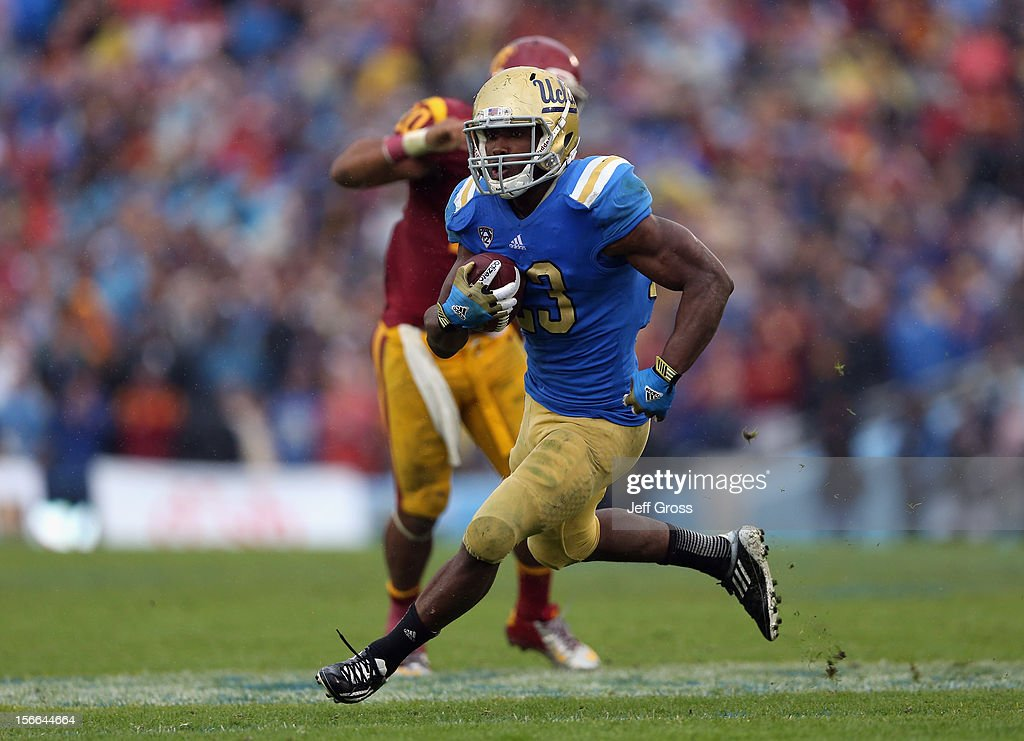 Running back <a gi-track='captionPersonalityLinkClicked' href=/galleries/search?phrase=Johnathan+Franklin&family=editorial&specificpeople=6235681 ng-click='$event.stopPropagation()'>Johnathan Franklin</a> #23 of the UCLA Bruins carries the ball enroute to a touchdown against the USC Trojans in the second half at the Rose Bowl on November 17, 2012 in Pasadena, California. UCLA defeated USC