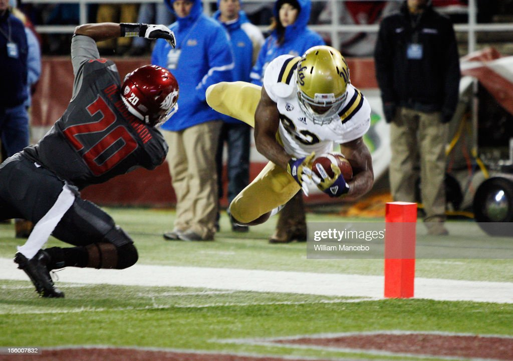 Running back Johnathan Franklin #23 of the UCLA Bruins leaps past safety Deone Bucannon #20 of the Washington State Cougars making a first down to the one yard line later declared a touchdown during the second quarter of play at Martin Stadium on November 10, 2012 in Pullman, Washington.