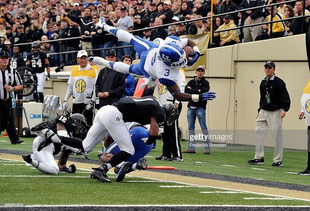 Running back Jojo Kemp #3 of the Kentucky Wildcats dives over the defense of the Vanderbilt Commodores at Vanderbilt Stadium on November 16, 2013 in Nashville, Tennessee.