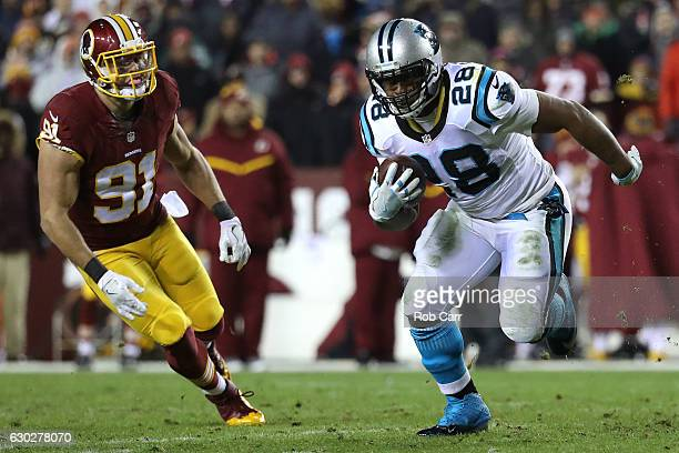 Running back Jonathan Stewart of the Carolina Panthers carries the ball against outside linebacker Ryan Kerrigan of the Washington Redskins in the...