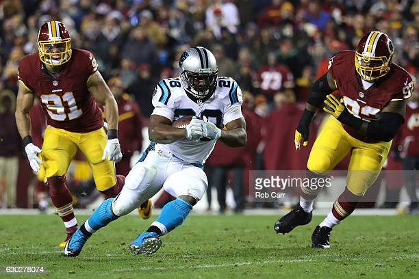 Running back Jonathan Stewart of the Carolina Panthers carries the ball against outside linebacker Ryan Kerrigan and defensive end Chris Baker of the...