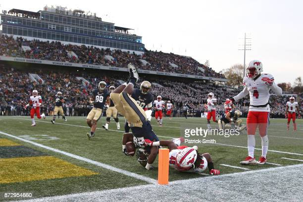 Running back Josh Brown of the Navy Midshipmen is tackled by Anthony Rhone of the Southern Methodist Mustangs in the first quarter at NavyMarines...