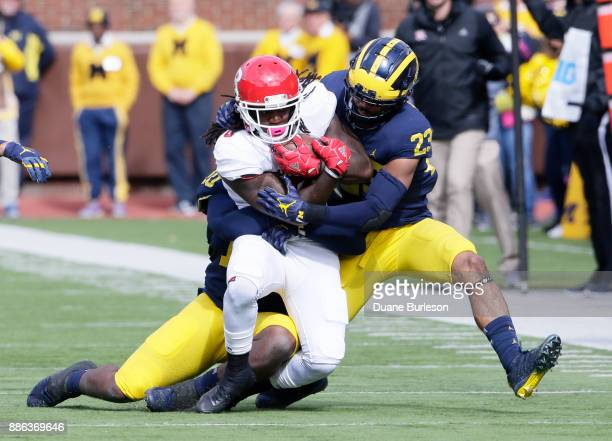 Running back Josh Hicks of the Rutgers Scarlet Knights is tackled by linebacker Devin Bush and defensive back Tyree Kinnel of the Michigan Wolverines...