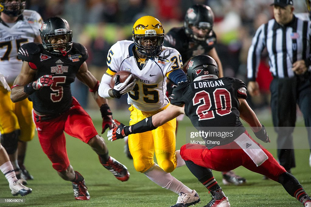 Running back Julian Durden #35 of the Kent State Golden Flashes looks to maneuver by defensive back Cole Lorigan #20 of the Arkansas State Red Wolves on January 6, 2013 at Ladd-Peebles Stadium in Mobile, Alabama. At halftime Arkansas State leads Kent State 14-10.