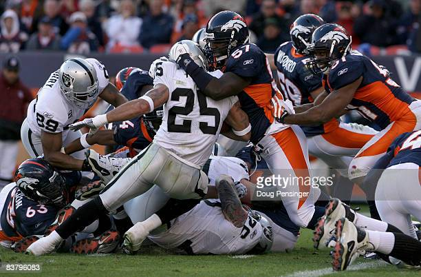 Running back Justin Fargas of the Oakland Raiders is stopped short of the goal line by linebacker Mario Haggan of the Denver Broncos as he rushes on...