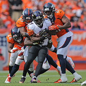 Running back Justin Forsett of the Baltimore Ravens is tackled by Darian Stewart David Bruton and Aqib Talib of the Denver Broncos at Sports...