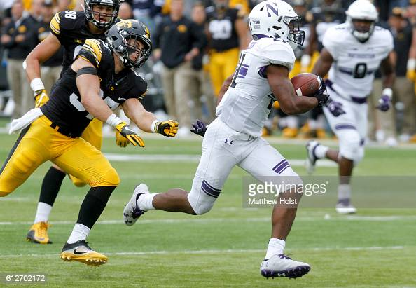 Running back Justin Jackson of the Northwestern Wildcats breaks a tackle on a touchdown run in the third quarter by defensive back Brandon Snyder of...