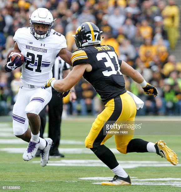 Running back Justin Jackson of the Northwestern Wildcats runs up the field in the first quarter in front of defensive back Brandon Snyder of the Iowa...