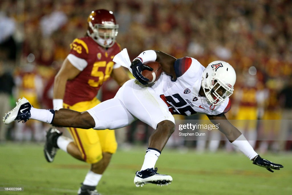 Running back Ka'Deem Carey #25 of the Arizona Wildcats tries to keep his balance as he carries the ball against defensive end J.R. Tavai #58 of the USC Trojans at Los Angeles Coliseum on October 10, 2013 in Los Angeles, California.