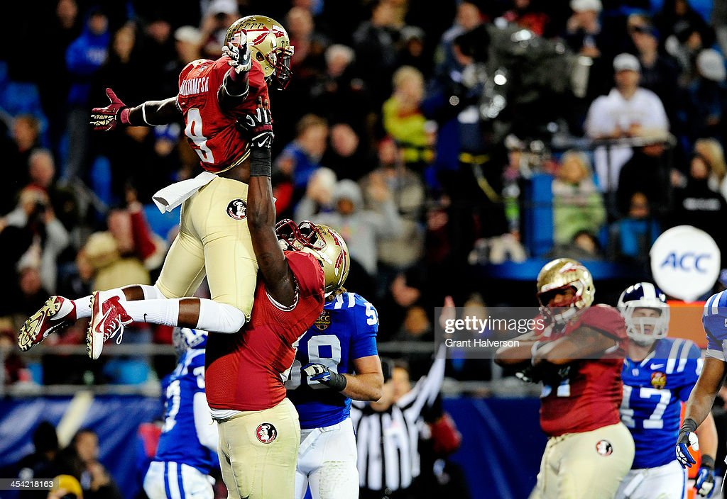 Running back Karlos Williams #9 celebrates a touchdown with offensive lineman Cameron Erving #75 of the Florida State Seminoles in the second quarter against the Duke Blue Devils during the ACC Championship game at Bank of America Stadium on December 7, 2013 in Charlotte, North Carolina.