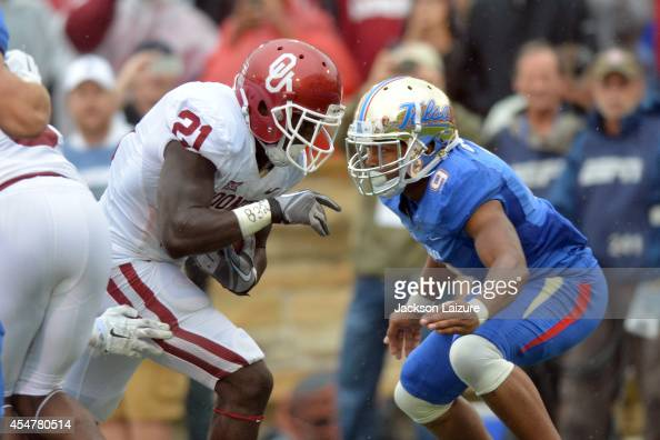 Running back Keith Ford of the Oklahoma Sooners runs into defensive back Dwight Dobbins of the Tulsa Golden Hurricane for a first half touchdown on...