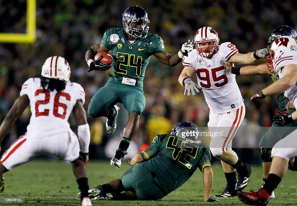 Running back Kenjon Barner #24 of the Oregon Ducks leaps over teammate David Paulson #42 in the second half against the Wisconsin Badgers at the 98th Rose Bowl Game on January 2, 2012 in Pasadena, California.