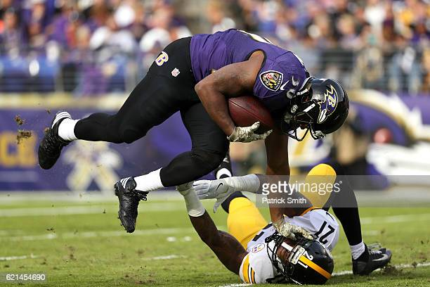 Running back Kenneth Dixon of the Baltimore Ravens carries the ball against strong safety Robert Golden of the Pittsburgh Steelers in the second...