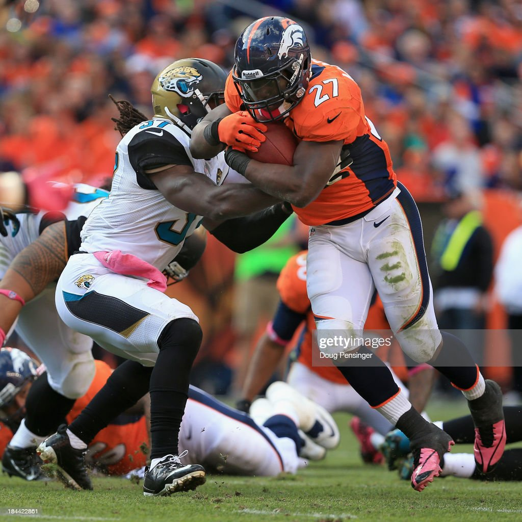 Running back <a gi-track='captionPersonalityLinkClicked' href=/galleries/search?phrase=Knowshon+Moreno&family=editorial&specificpeople=3986554 ng-click='$event.stopPropagation()'>Knowshon Moreno</a> #27 of the Denver Broncos breaks the tackle of strong safety <a gi-track='captionPersonalityLinkClicked' href=/galleries/search?phrase=John+Cyprien&family=editorial&specificpeople=11299770 ng-click='$event.stopPropagation()'>John Cyprien</a> #37 of the Jacksonville Jaguars and rushes eight yards for a touchdown in the third quarter at Sports Authority Field at Mile High on October 13, 2013 in Denver, Colorado. The Broncos defeated the Jaguars 35-19.
