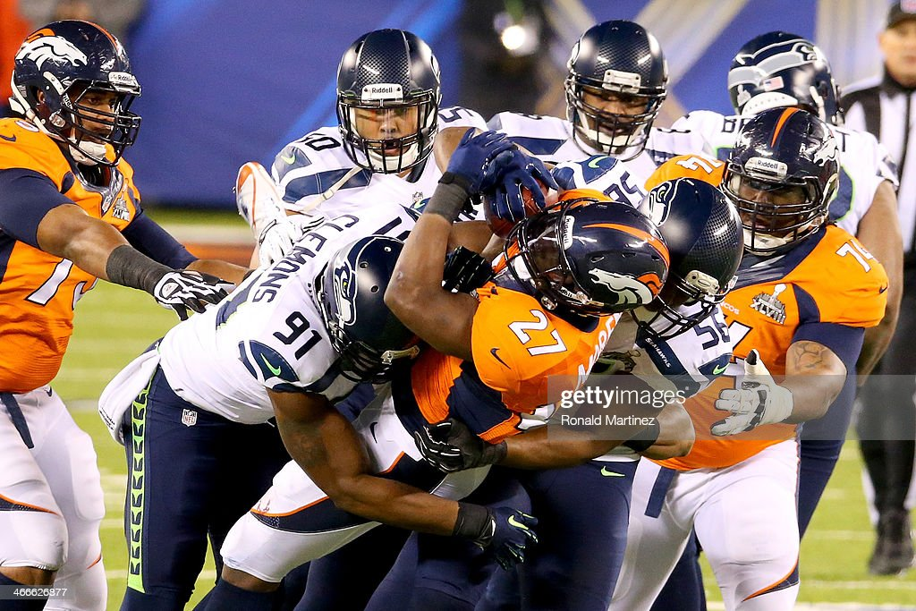 Running back <a gi-track='captionPersonalityLinkClicked' href=/galleries/search?phrase=Knowshon+Moreno&family=editorial&specificpeople=3986554 ng-click='$event.stopPropagation()'>Knowshon Moreno</a> #27 of the Denver Broncos is tackled by <a gi-track='captionPersonalityLinkClicked' href=/galleries/search?phrase=Chris+Clemons+-+American+Football+Defensive+End&family=editorial&specificpeople=9844895 ng-click='$event.stopPropagation()'>Chris Clemons</a> #91, defensive end <a gi-track='captionPersonalityLinkClicked' href=/galleries/search?phrase=Cliff+Avril&family=editorial&specificpeople=2237705 ng-click='$event.stopPropagation()'>Cliff Avril</a> #56 and outside linebacker K.J. Wright #50 of the Seattle Seahawks in the first quarter during Super Bowl XLVIII at MetLife Stadium on February 2, 2014 in East Rutherford, New Jersey.