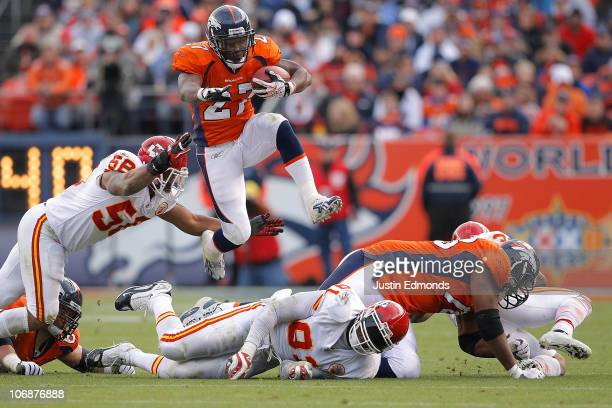 Running back Knowshon Moreno of the Denver Broncos jumps over a pile of defenders and past linebacker Derrick Johnson of the Kansas City Chiefs...