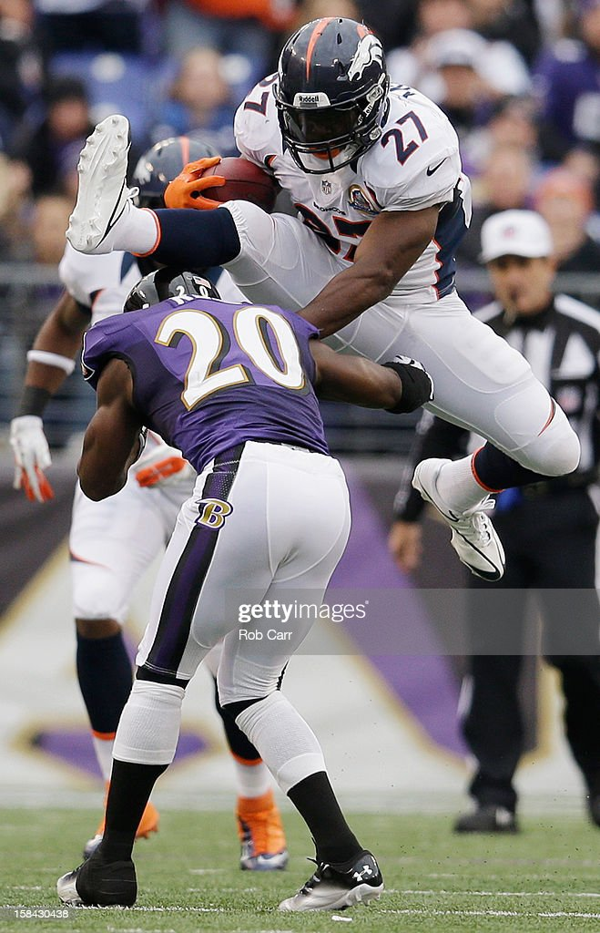 Running back Knowshon Moreno #27 of the Denver Broncos jumps over free safety Ed Reed #20 of the Baltimore Ravens while rushing the ball during the first half at M&T Bank Stadium on December 16, 2012 in Baltimore, Maryland.