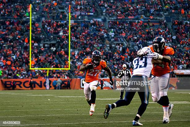 Running back Knowshon Moreno of the Denver Broncos runs in the open field as offensive tackle Orlando Franklin blocks safety Michael Griffin of the...