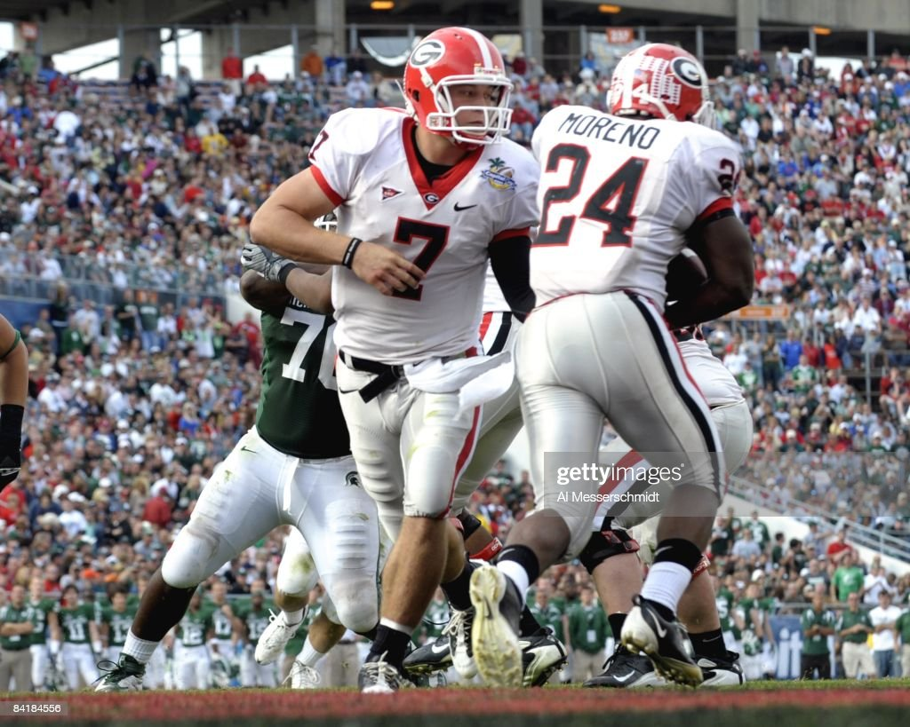 Running back Knowshon Moreno of the University of Georgia takes a handoff from quarterback Matthew Stafford against the Michigan State Spartans at...