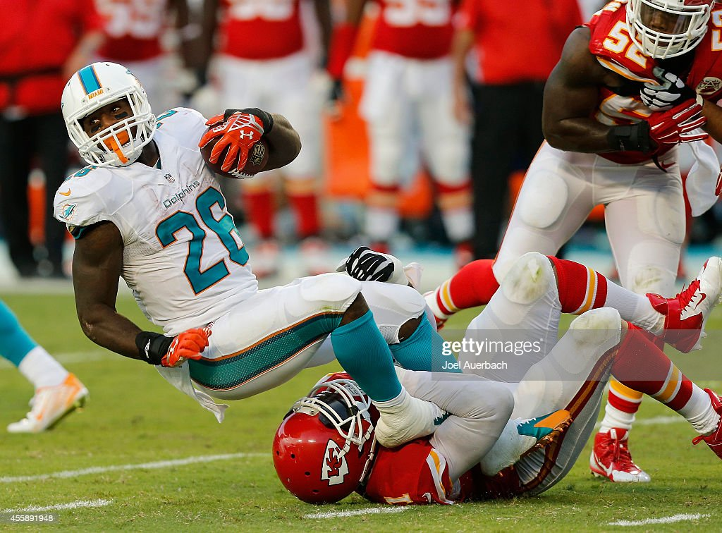 Running back Lamar Miller #26 of the Miami Dolphins is brought down by outside linebacker Tamba Hali #91 of the Kansas City Chiefs in the first half at Sun Life Stadium on September 21, 2014 in Miami Gardens, Florida.