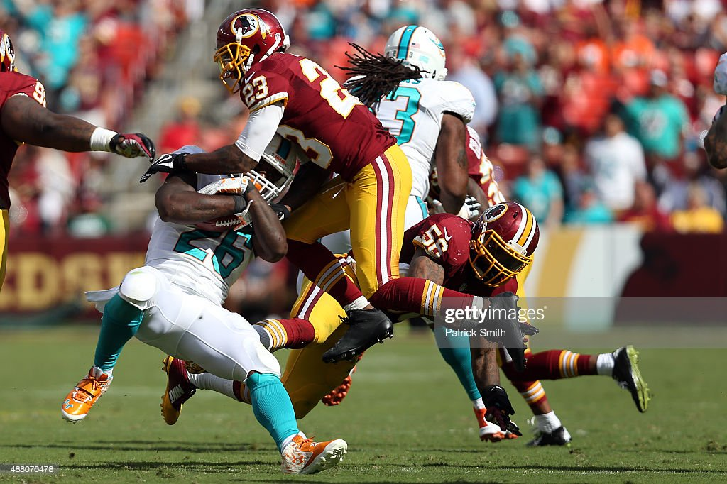 Running back Lamar Miller of the Miami Dolphins is tackled by cornerback DeAngelo Hall of the Washington Redskins in the second half of a game at...