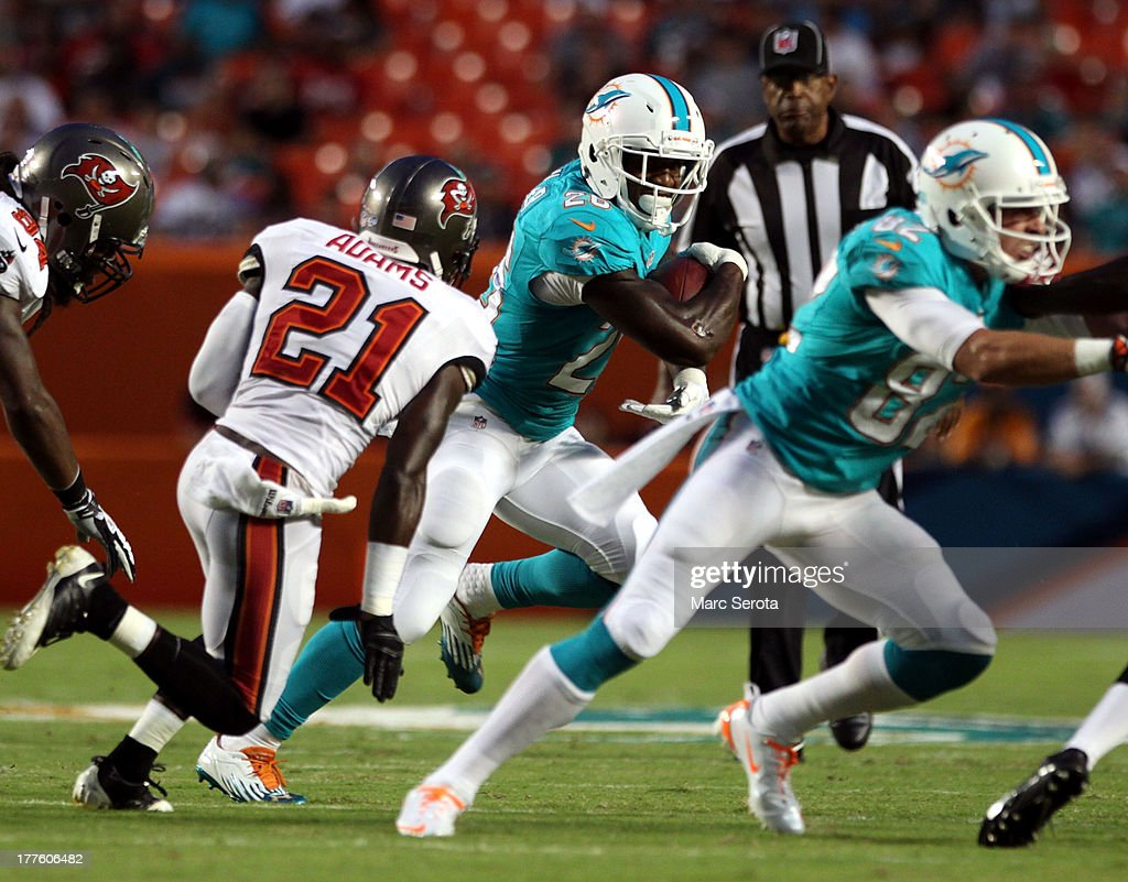 Running back Lamar Miller #26 of the Miami Dolphins rushes against the Tampa Bay Buccaneers at Sun Life Stadium on August 24, 2013 in Miami Gardens, Florida.