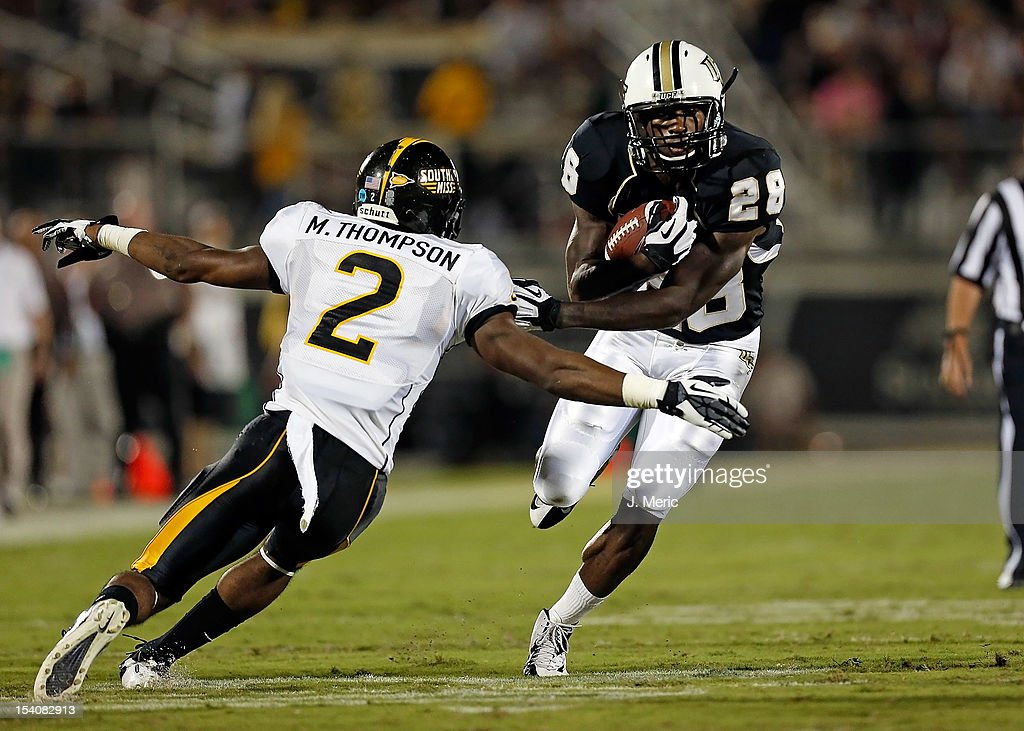 Running back Latavius Murray #28 of the Central Florida Knights runs out of the tackle of defender Martez Thompson #2 of the Southern Mississippi Golden Eagles during the game at Bright House Networks Stadium on October 13, 2012 in Orlando, Florida.