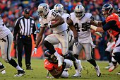 Running back Latavius Murray of the Oakland Raiders rushes against the Denver Broncos during a game at Sports Authority Field at Mile High on...