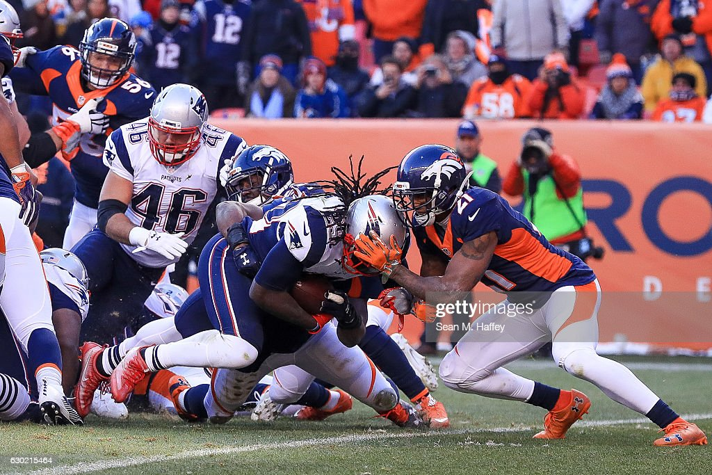 Running back LeGarrette Blount #29 of the New England Patriots dives into the end zone for a second quarter 1-yard rushing touchdown while defended by cornerback Aqib Talib #21 of the Denver Broncos at Sports Authority Field at Mile High on December 18, 2016 in Denver, Colorado.