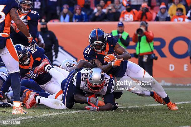 Running back LeGarrette Blount of the New England Patriots is hit by cornerback Aqib Talib of the Denver Broncos after diving across the goal line...